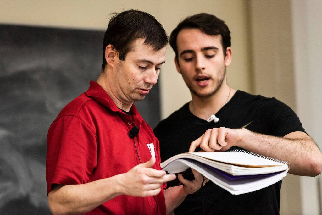 Matt Bowman and student look over a textbook together