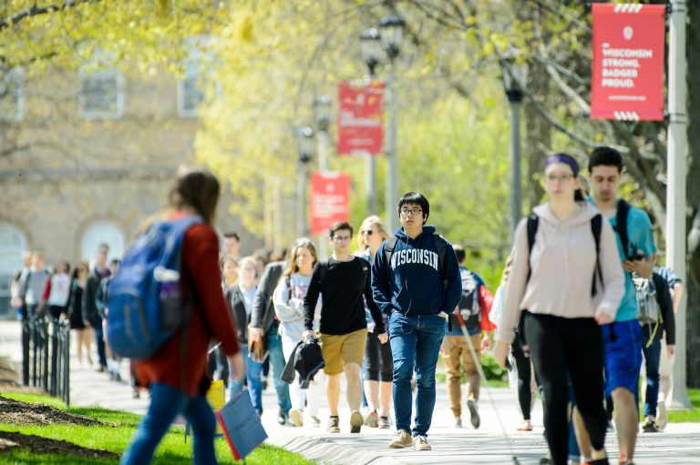 Students walk down the sidewalk of Bascom Hill during spring at the University of Wisconsin-Madison