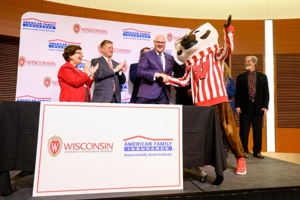 UW Chancellor Rebecca Blank and Jack Salzwede, Chairman and CEO of American Family Insurance, are joined by UW mascot Bucky Badger after they sign a letter of intent.
