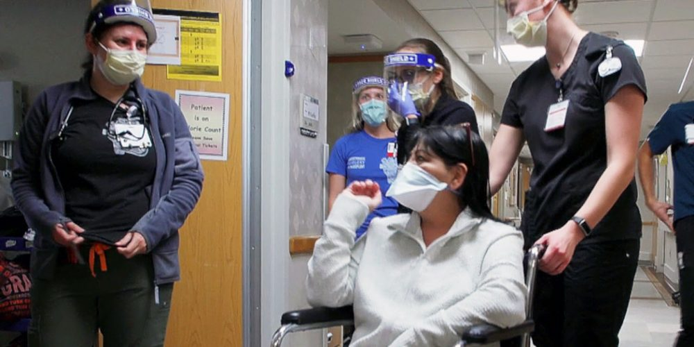 Lung transplant patient wearing mask in wheelchair with healthcare staff
