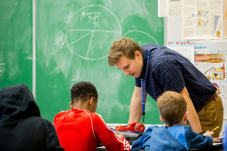 Student teacher working with children in classroom